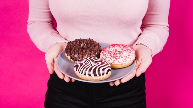 Mid section of a woman holding plate of various tasty donuts in hand against pink background