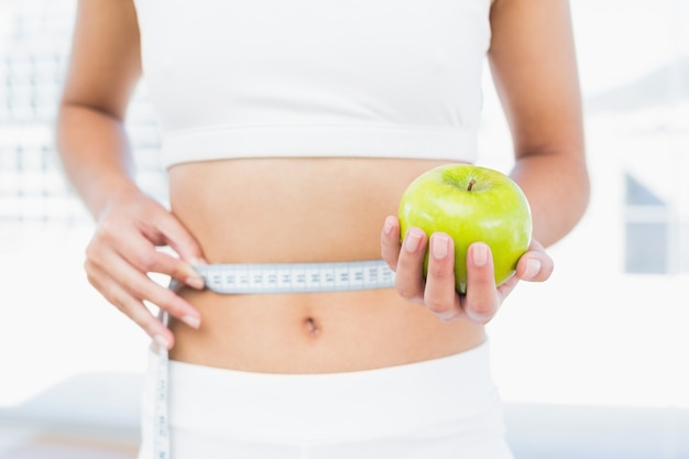 Mid section of woman measuring waist as she holds apple