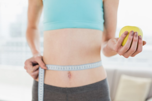 Mid section of woman measuring waist with apple in hand