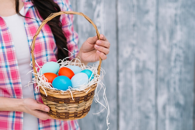 Mid section of woman's hand holding colorful easter eggs in the basket against blurred background