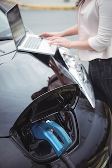 Mid section of woman using laptop while charging electric car