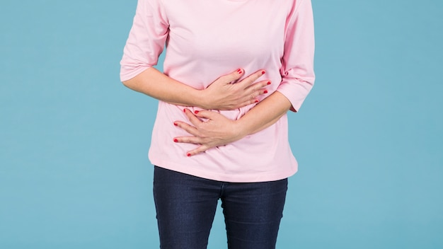 Mid-section of a woman with stomach ache standing against blue background