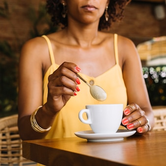 Mid section of woman with white cappuccino cup