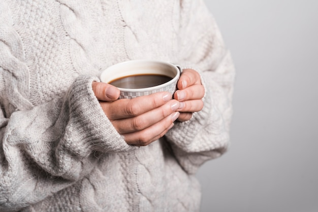 Mid section of woman in woolen clothes holding coffee cup