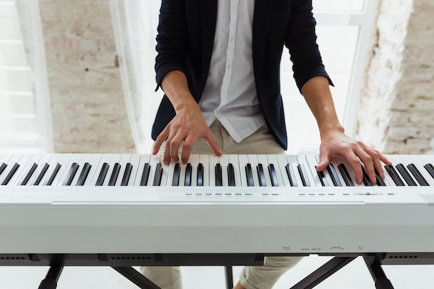 Mid section of a young man playing the grand piano keyboard