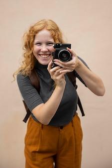 Metà di donna corta che mostra la macchina fotografica