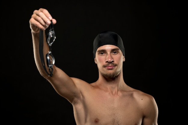 Mid shot of athlete holding goggles