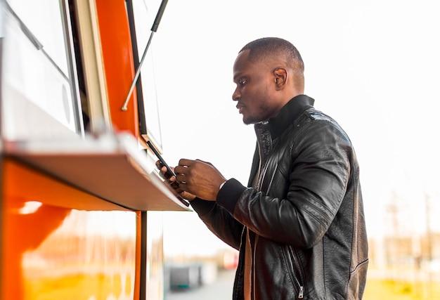 Черный мужчина в середине кадра делает заказ на грузовике с едой