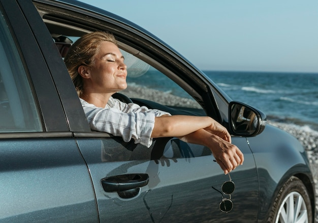 Mid shot blonde woman in car looking at sea