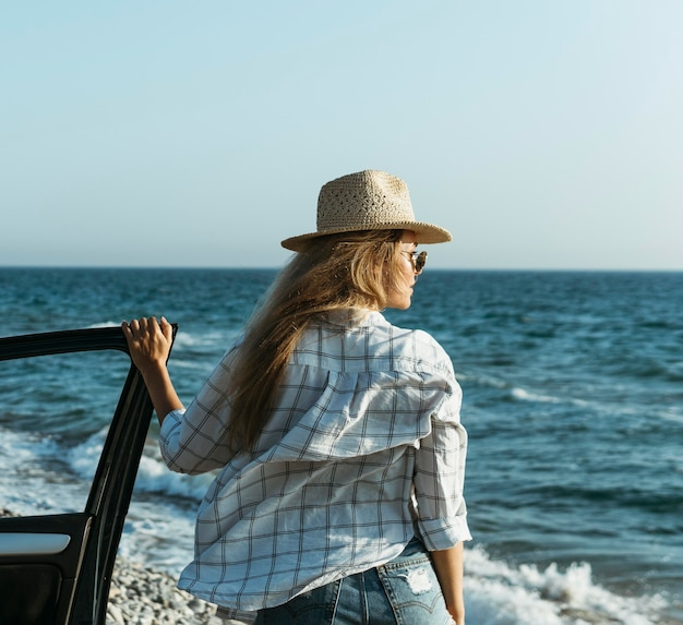 Mid shot blonde woman looking at sea by car
