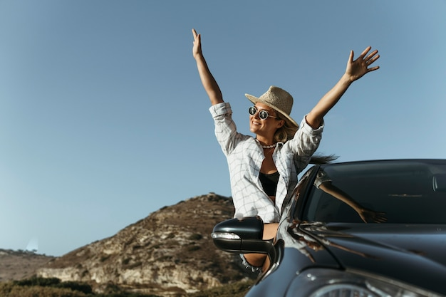 Mid shot blonde woman out of car window with hands in the air