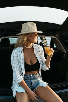 Mid shot blonde woman standing in car trunk with juice bottle