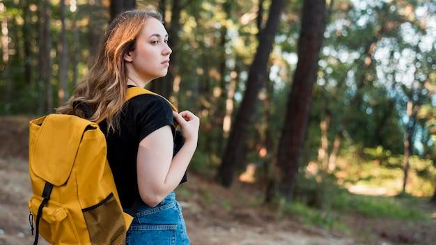 森のバックパックで半ばショットブロンドの女性