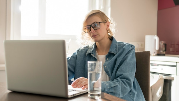 Середине выстрел блондинка работает на ноутбуке в кухне