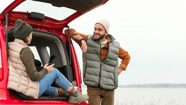 Парень в середине кадра стоит рядом с подругой, сидящей в багажнике