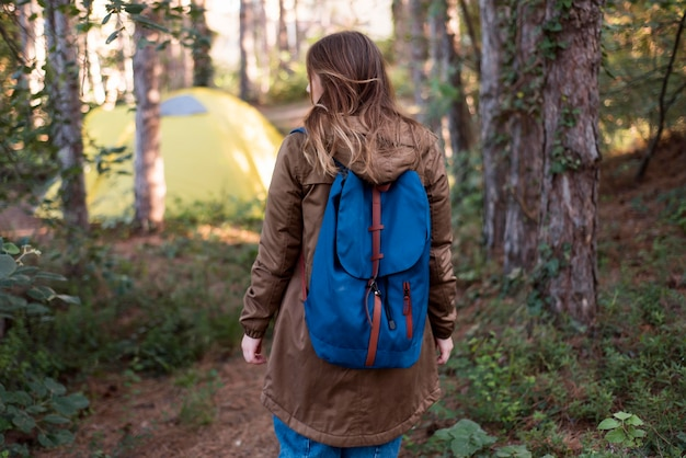 Mid shot brown haired girl walking to tent