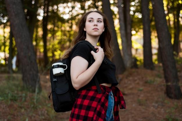 Donna dai capelli castani a metà colpo nella foresta