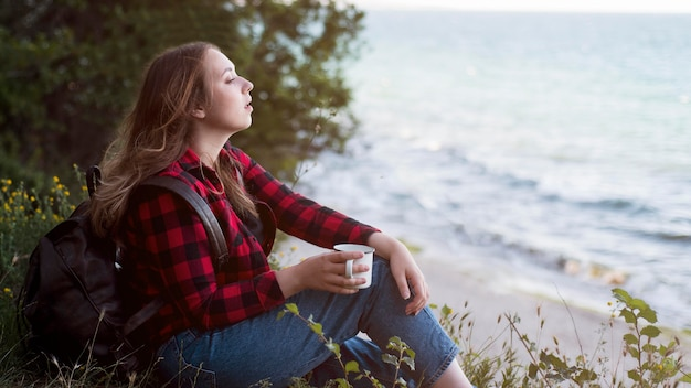海を見て地面に座っている半ばショットの茶色の髪の女性