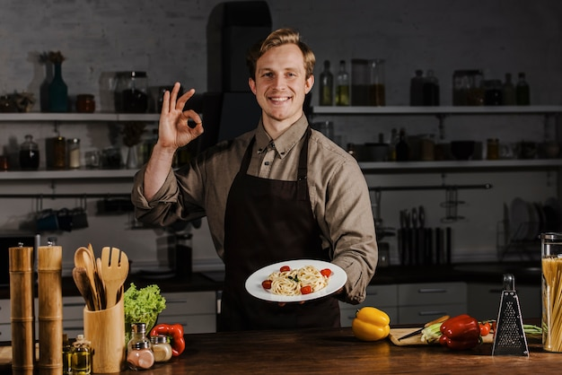 Mid shot chef holding plate with pasta and making ok sign