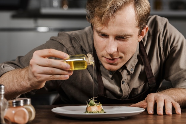 Mid shot chef plating dish with olive oil