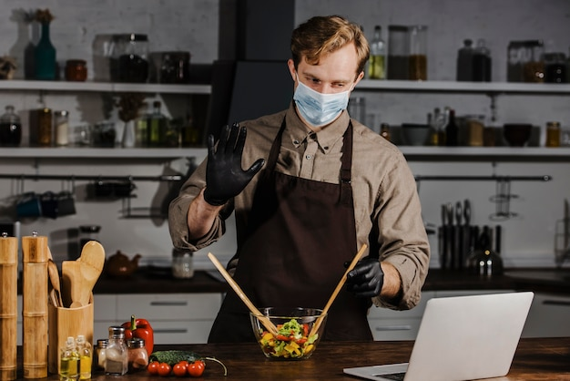 Mid shot chef with mask mixing salad ingredients looking at laptop