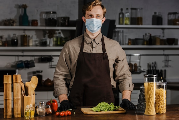 Mid shot chef with mask and salad
