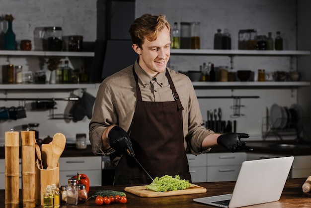 Mid shot chef with salad looking at laptop