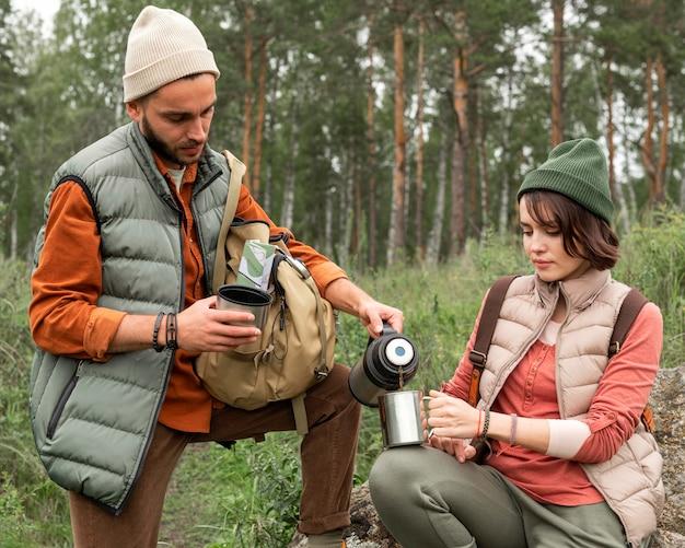 Пара в середине выстрела, разливая горячий напиток на природе