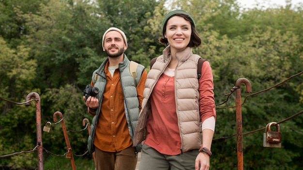 木製の橋の上を歩くミディアムショットのカップル