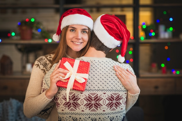 Mid shot couple wearing santa hats hugging eachother