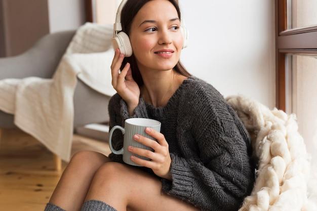 Donna accogliente del colpo medio con la tazza che ascolta la musica