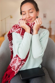 Mid shot cozy woman with scarf in armchair