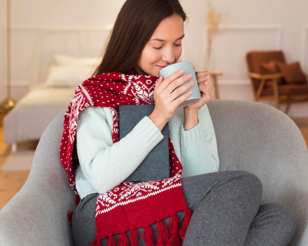 Mid shot cozy woman with scarf and mug