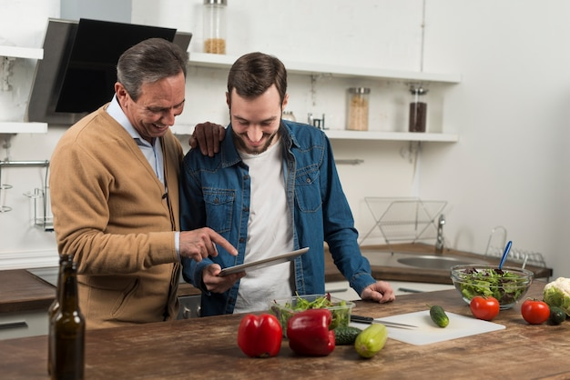 Mid shot father and son looking at tablet in kitchen