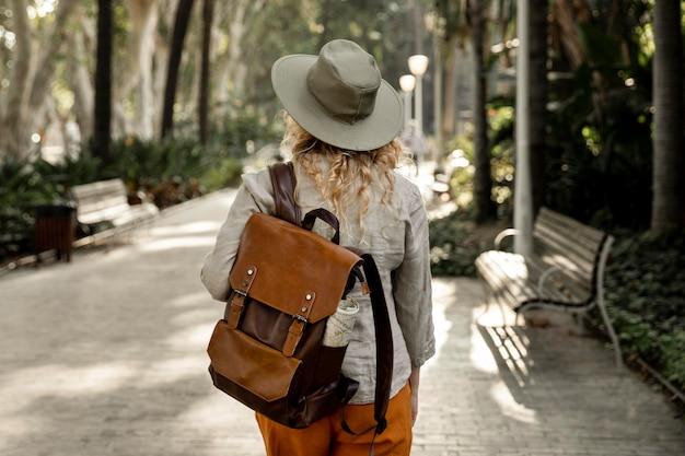 自然の中を歩く帽子とミディアムショットの女性