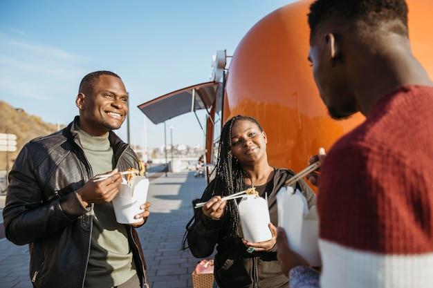 Друзья в середине кадра едят китайскую еду возле фургона с едой