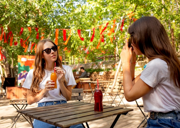 フレッシュジュースのボトルを持って写真を撮るミディアムショットの友達