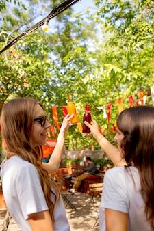 Amici a metà colpo che tengono le bottiglie di succo di frutta fresco nel parco