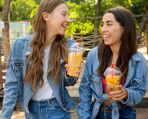Mid shot friends holding fresh juice and laughing