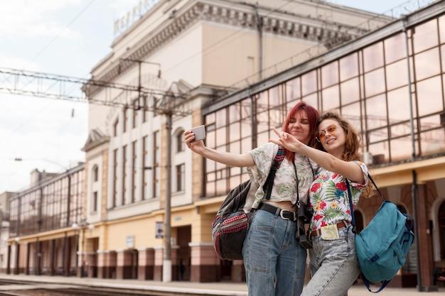 Mid shot friends taking selfie at train station