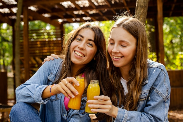 Mid shot friends with fresh juice bottles