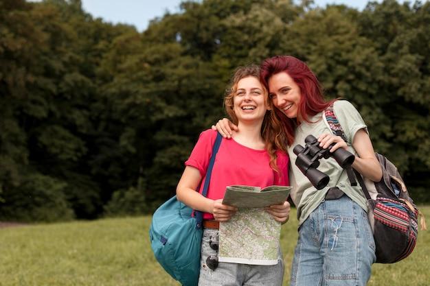 Девушки в середине кадра с биноклем и картой на природе