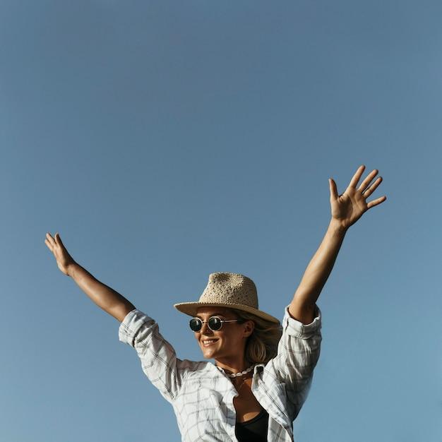 空気中の手でミディアムショット幸せなブロンドの女性