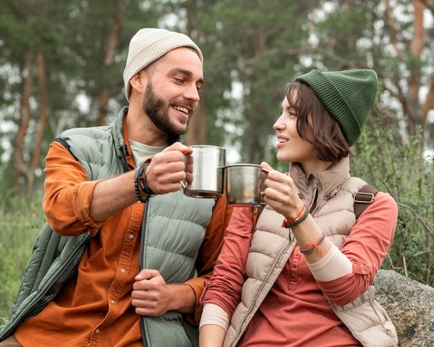 Середина выстрела счастливая пара, наслаждаясь горячим напитком на природе