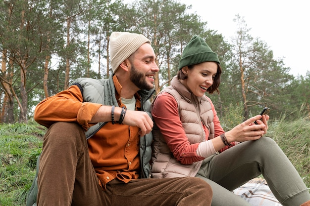 Середина кадра счастливая пара сидит на траве и смотрит на телефон