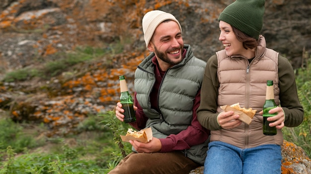 Середина кадра счастливая пара сидит на скале, пьёт и ест
