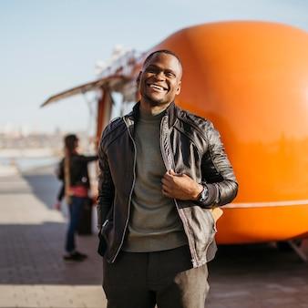 Счастливый мужчина в середине кадра перед грузовиком с едой