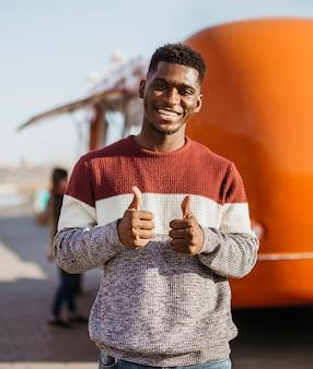 Uomo felice a metà tiro davanti al camion di cibo
