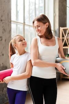 Середина выстрела счастливая мама и девушка держат коврики для йоги