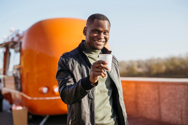 Мужчина в середине кадра держит чашку кофе перед грузовиком с едой
